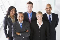Group of co-workers standing in office space smiling (high key) - stock photo