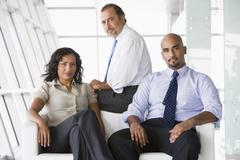 Three businesspeople sitting indoors (high key/selective focus) - stock photo