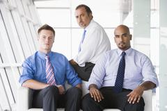 Three businessmen sitting indoors (high key/selective focus) - stock photo