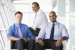 Three businessmen sitting indoors smiling (high key/selective focus) - stock photo