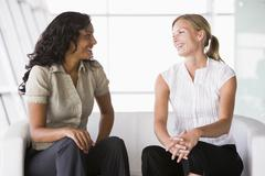 Two businesswomen sitting indoors talking and smiling (high key/selective focus) - stock photo