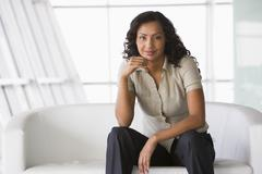 Businesswoman sitting indoors smiling (high key/selective focus) - stock photo