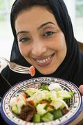 Woman holding bowl of salad and smiling (high key/selective focus) Stock Photos