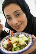 Woman holding bowl of salad and smiling (high key/selective focus) - stock photo
