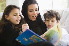 Mother and two young children in living room reading book (high key/selective Stock Photos