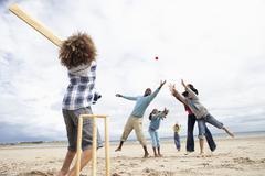 Perhe pelissä kriketti rannalla Kuvituskuvat