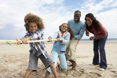 Stock Photo of family playing tug of war on beach