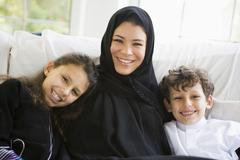Mother and two young children sitting in living room smiling (high key/selective - stock photo