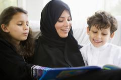 Mother and two young children in living room reading book and smiling (high Stock Photos