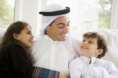 Father and two young children sitting in living room smiling (high key/selective Stock Photos