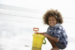 Happy boy at beach with bucket and spade Stock Photos