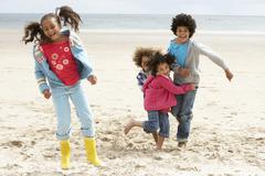 Happy children playing on beach Stock Photos