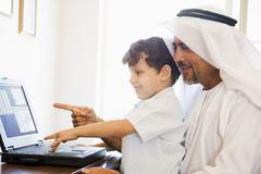 Man and young boy in office with laptop pointing and smiling (high key/selective Stock Photos