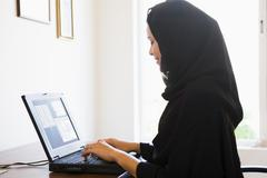 Stock Photo of Woman in office with laptop smiling (high key/selective focus)