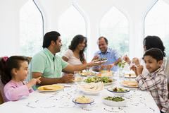 Family sitting at dinner table smiling (high key) - stock photo
