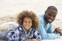 father and son laying on beach - stock photo