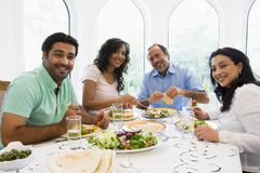 Two couples sitting at dinner table smiling (high key) Stock Photos