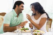 Couple sitting at dinner table smiling (high key) Stock Photos