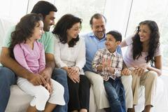 Family sitting in living room smiling (high key) Stock Photos