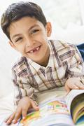 Young boy in living room reading a book and smiling (high key) - stock photo