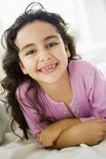 Stock Photo of Young girl in living room smiling (high key)