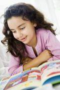 Stock Photo of Young girl in living room reading book and smiling (high key/selective focus)