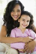 Mother and daughter in living room smiling (high key) - stock photo