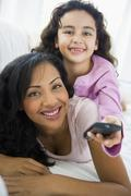 Mother and daughter in living room with remote control smiling (high Stock Photos