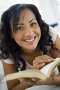 Woman in living room with book smiling (high key/selective focus) - stock photo