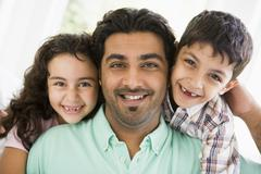 Father and two young children in living room smiling (high key) Stock Photos