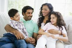 Family in living room sitting on sofa smiling (high key) Stock Photos