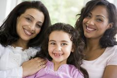 Two women and young girl in living room embracing and smiling (high key) - stock photo