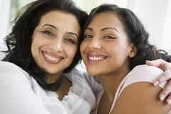 Two women in living room embracing and smiling (high key) Stock Photos