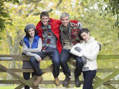 young friends sitting on fence - stock photo