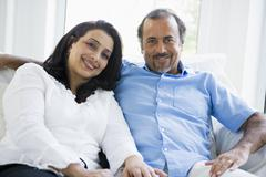Couple sitting in living room smiling (high key) - stock photo