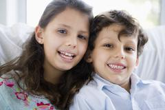 Two young children in living room smiling (high key) Stock Photos