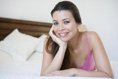 Woman relaxing on bed in bedroom smiling (selective focus) - stock photo