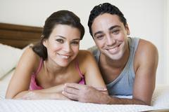 Couple relaxing on bed in bedroom smiling (selective focus) - stock photo