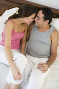 Couple relaxing on bed in bedroom snuggling and smiling (selective focus) - stock photo