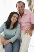 Couple in living room smiling (high key) Stock Photos