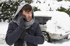 Young man in snow with broken down car Stock Photos