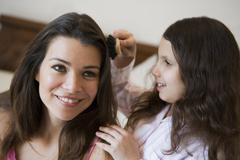 Young girl brushing woman's hair on bed in bedroom smiling (selective focus) - stock photo