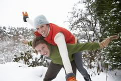 young couple having fun in snow - stock photo