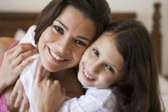 Woman and young girl in bedroom embracing and smiling (selective focus) - stock photo