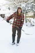 Young man clearing snow Stock Photos