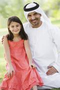Man and young girl outdoors in a park smiling (selective focus) - stock photo
