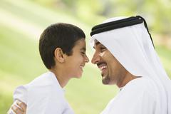 Man and young boy outdoors in park smiling (selective focus) - stock photo