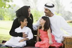 Family outdoors in park having a picnic and smiling (selective focus) - stock photo