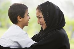 Mother and son outdoors in park embracing and smiling (selective focus) - stock photo