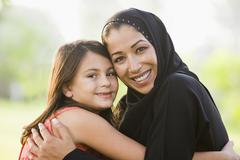 Mother and daughter outdoors in park embracing and smiling (selective focus) - stock photo